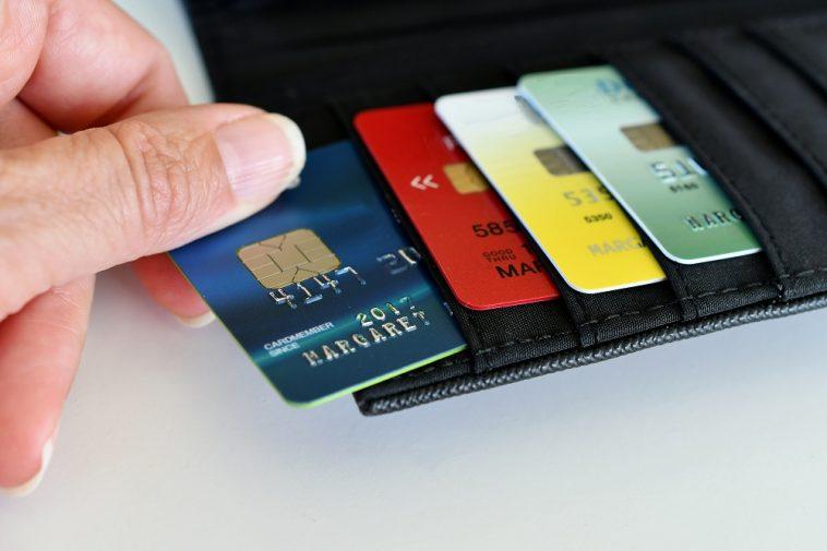 mão de mulher pegando um cartão de crédito para negativados em sua carteira, com outros três cartões
