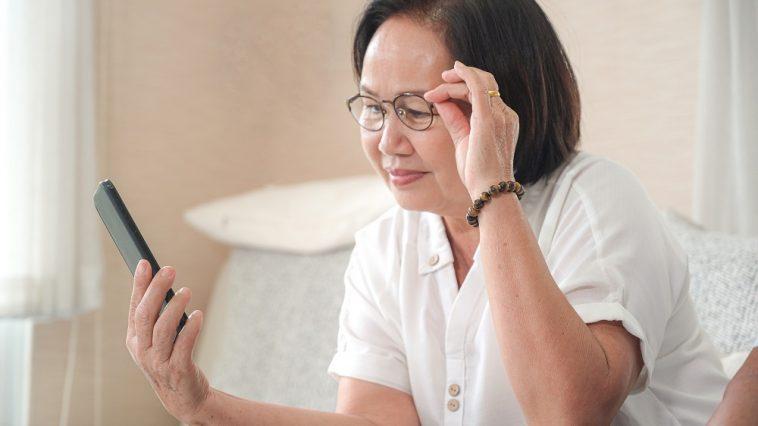 Mulher asiática idosa sentada no sofá está chamando uma chamada de vídeo no smartphone simulando a prova de vida do INSS