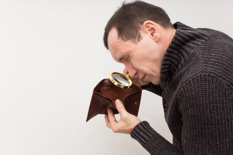 homem olhando com uma lupa a carteira vazia, simbolizando o atraso no calendário de pagamento do auxílio emergencial 2021