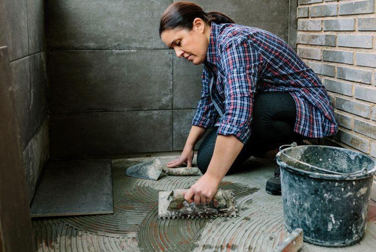 mulher colocando piso na casa mostrando que é possível reformar casa gastando pouco