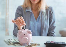 mulher colocando moeda em cofre rosa, simulando guardar dinheiro de emergência