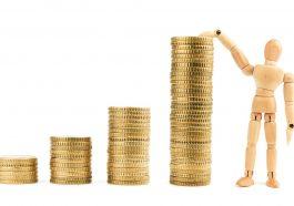 moedas de ouro empilhadas em ordem crescente com modelo de madeira simulando o crescimento dos juros no Brasil