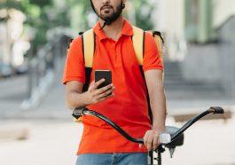 entregador acessando o aplicativo no celular, mostrando que trabalha para fazer uma renda extra