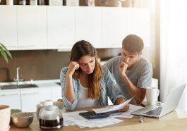 Casal de família triste percebendo suas dívidas com cheque especial, olhando atentamente em documentos, calculando sua família