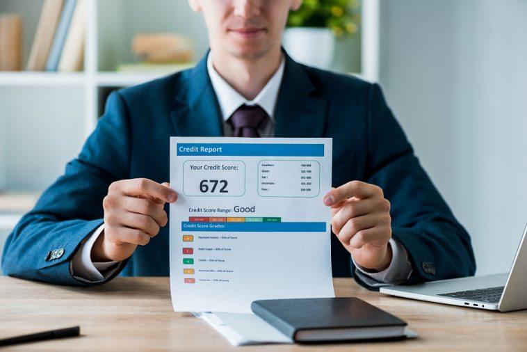 homem segurando uma folha mostrando seu score de crédito do Serasa com pontuação 672