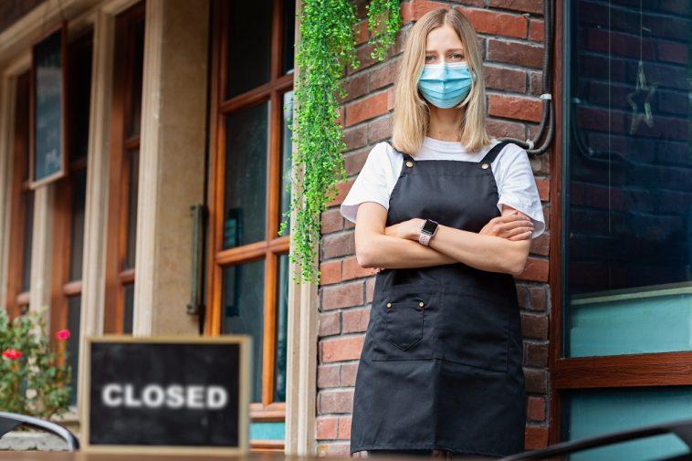 mulher de máscara em frente à um restaurante com a placa de fechado, indicando a crise de desemprego no Brasil