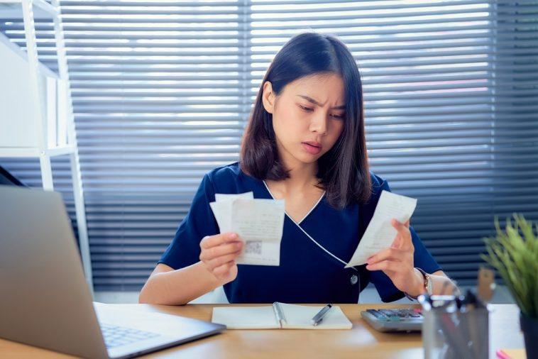 mulher olhando as contas e pensando em como limpar o nome sujo