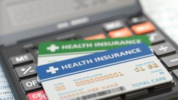 duas carteirinhas de plano de saúde em cima de uma calculadora ao fundo mais desfocada