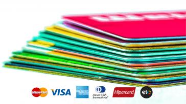 cartões de crédito empilhados ao fundo e mais a frente algumas bandeiras de cartão de crédito