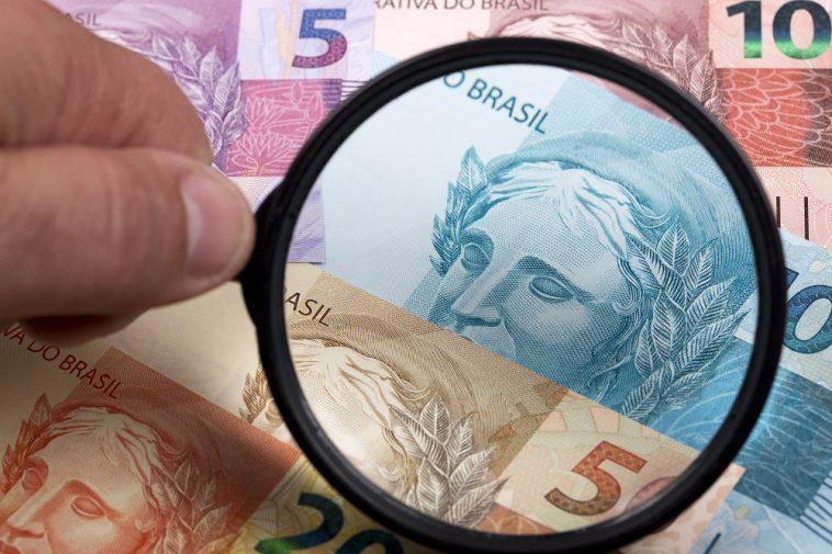 lupa sob notas de dinheiro falsas