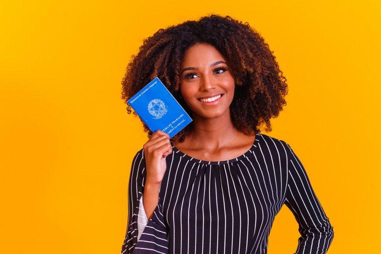 mulher jovem segurando uma carteira de trabalho