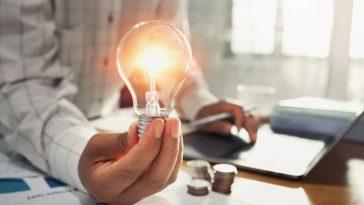 homem ao fundo segurando uma lâmpada em uma mesa com contas e moedas