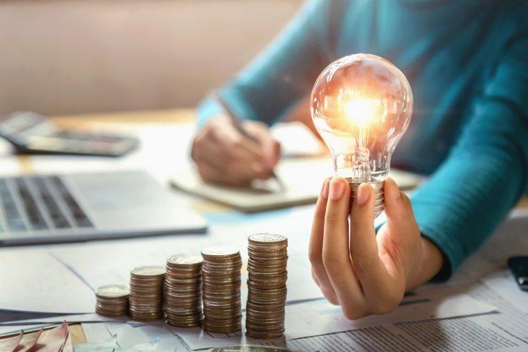 mulher segurando lâmpada, fazendo contas e com pilhas de moedas a sua frente