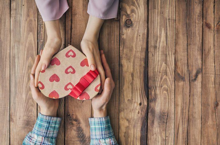mão de casal de namorados segurando uma caixa de coração de presente, simbolizando as compras no comércio mineiro no dia dos namorados