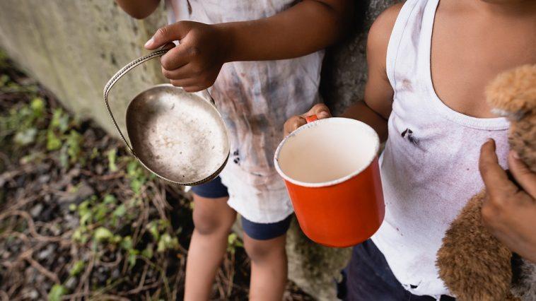 Visão recortada de crianças afro-americanas desabrigadas segurando copo