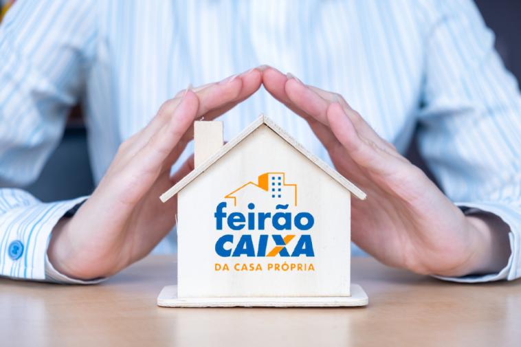 imagem de um homem de negócios apoiando a mão sob uma minuatura de casa com o logo do Feirão da Caixa de imóveis 2021
