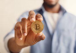 Bitcoin dourado em closeup de mão homem afro-americano