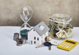modelo de casa com ampulheta, calculadora, dinheiro e chaves, conceito imobiliário