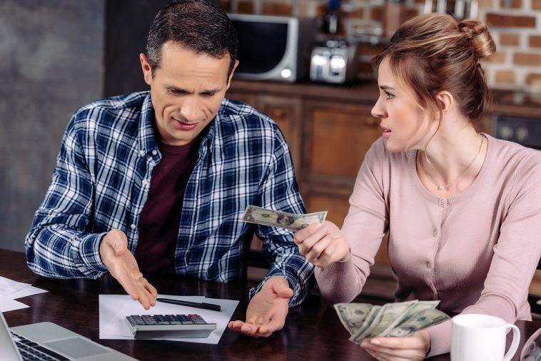 retrato de casal contando dinheiro enquanto está sentado na mesa em casa, conceito de problemas financeiros