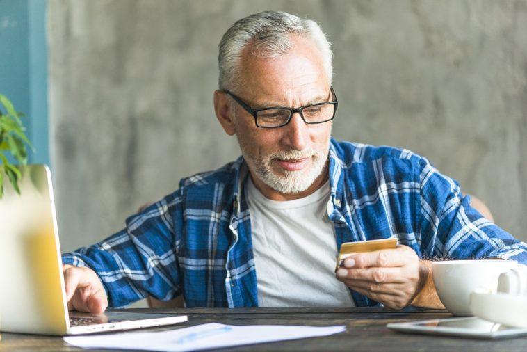 homem aposentado olhando para o seu cartão de crédito consignado