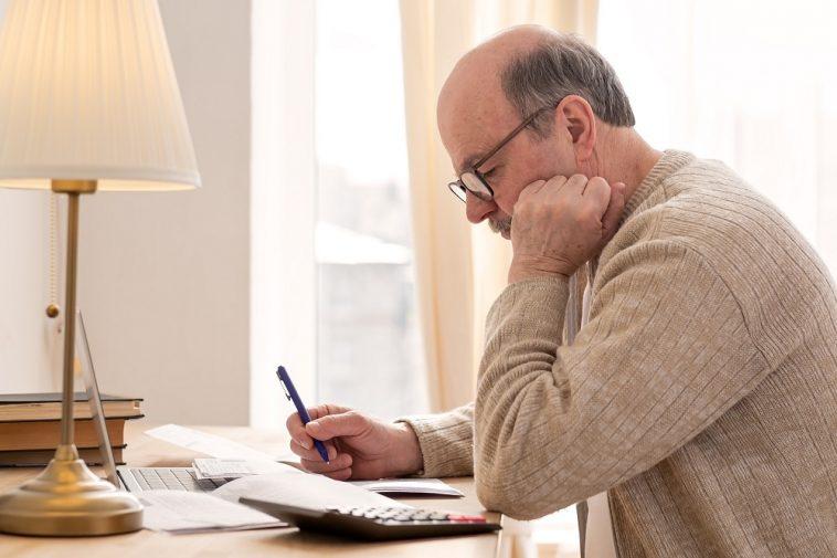 Homem sênior sentado com papelada e usando calculadora para fazer as contas de como sair do cheque especial
