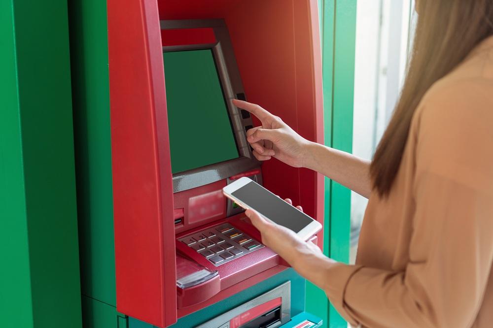 mulher usando o caixa eletrônico com o celular na mão para fazer uma recarga no Banco24Horas