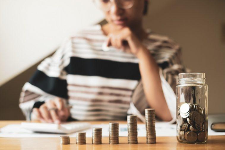 mulher ao fundo desfocado calculando na calculadora e a frente pilhas crescentes de moeda simbolizando guardar e investir dinheiro