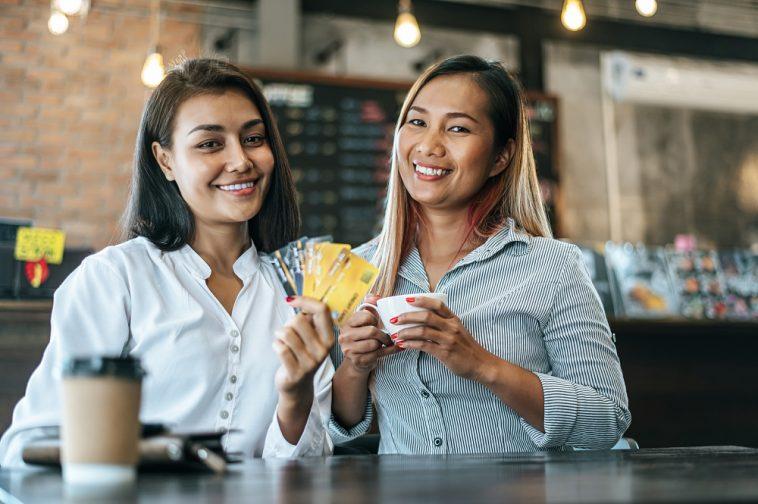 duas mulheres em uma cafeteria. Uma delas com vários cartões na mão, indicando a possibilidade de um cartão de crédito sem anuidade