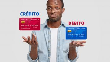 homem afrodescendente com expressão de dúvida e sob suas mãos dois cartões, simbolizando a escolha entre Cartão de crédito ou cartão de débito