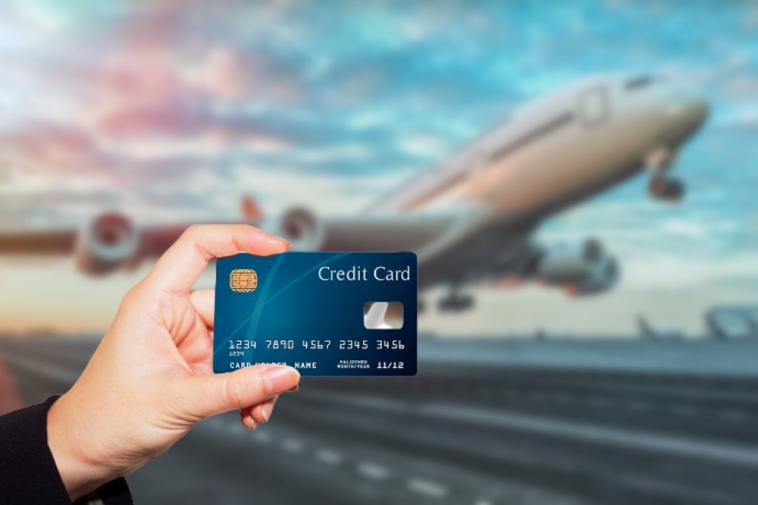 foto de avião decolando ao fundo desfocado e a frente mão segurando cartão de crédito simbolizando o programa de milhas aéreas