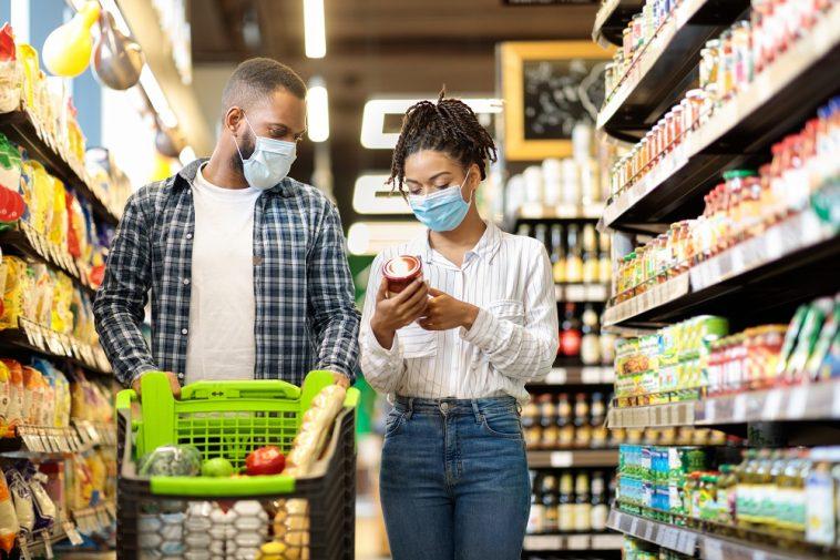 Casal afro-americano em máscaras comprando mantimentos comida no supermercado, simbolizando o preço da cesta básica no Brasil em Junho