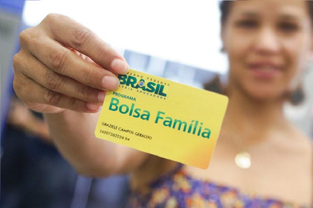 mulher segurando um cartão do novo Bolsa Família