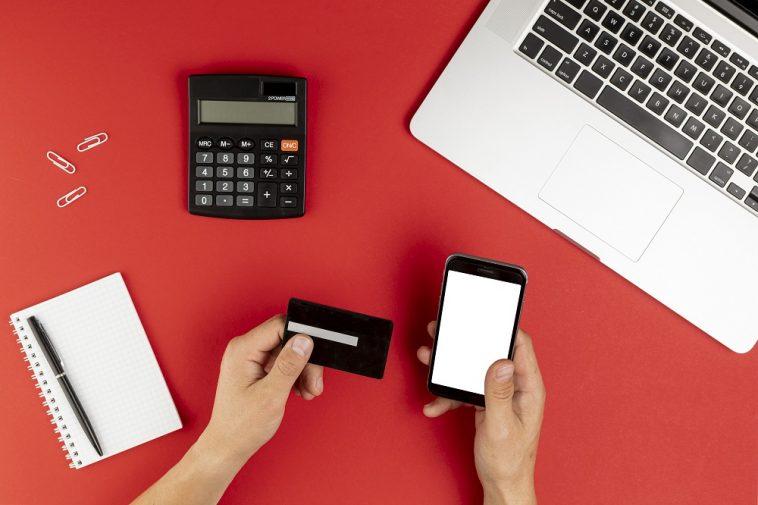 mão feminina segurando cartão de crédito e mexendo no celular, ao lado um bloco de anotações e calculadora