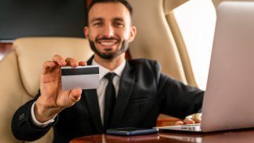 homem de terno em avião sentado exibindo seu cartão de crédito de alta renda