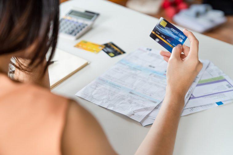 mulher segurando cartão de crédito na mão e em sua mesa boletos de contas para pagar
