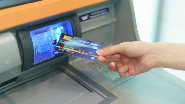 mão de mulher inserindo um cartão de crédito em um caixa eletrônico, para ilustrar o saque com cartão de crédito