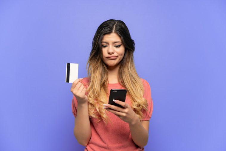 mulher mexendo no celular pesquisando como cancelar compra no cartão de crédito
