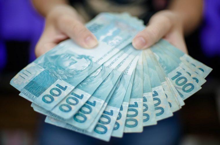 mulher mostrando na mão várias notas de cem reais após conseguir um empréstimo online