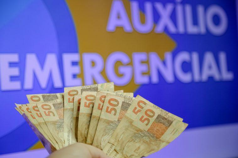 mão de pessoa com notas de cinquenta reais ao fundo de uma imagem escrita auxílio emergencial, simbolizando opagamento da quinta parcela do auxílio emergencial