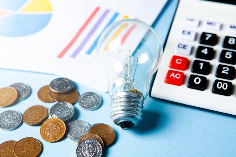 lâmpada em cima de uma mesa e na volta algumas moedas e calculadora representando a nova bandeira tarifária aumento conta de luz
