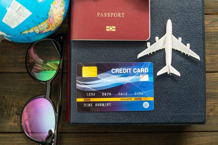 Cartão de crédito internacional e modelo do avião na mesa de madeira, preparação para o conceito de viagem