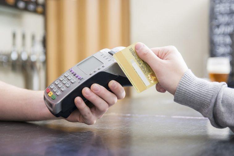 Imagem recortada de uma pessoa pagando com cartão de crédito em uma maquininha de cartão