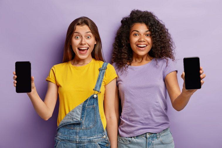 dois adolescentes multiétnicos sorridentes se aproximam, mostram smartphones com telas de maquete para seu texto sobre como escolher o celular ideal