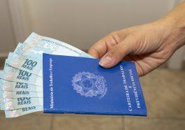 carteira de trabalho com dinheiro notas de cem reais dentro demostrando as novas vagas de emprego no Brasil