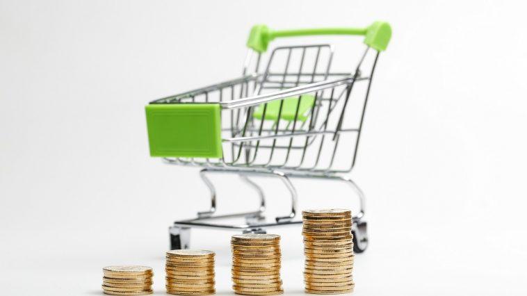 carrinho de supermercado verde ao fundo e na frente pilhas de moedas aumentando simbolizando a inflação nas alturas aumenta preços