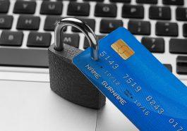 cadeado de bloqueio com cartão de crédito em cima do laptop simbolizando a proteção de um seguro de cartão de crédito
