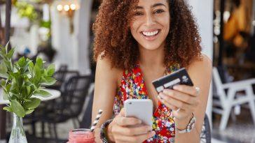 mulher jovem feliz e sorridente com penteado afro, usa um celular moderno e um cartão de crédito para fazer compras online