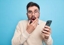 Homem europeu adulto barbudo estupefato mantém a boca aberta e olha fixamente aterrorizado, segura o celular descobre notícias chocantes vestido com um macacão casual