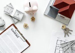 mesa branca e em cima uma mini casa, dólares, um contrato bancário de financiamento e um cofre de porco rosa
