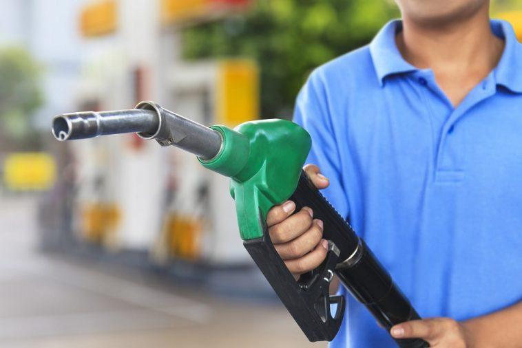 Frentista desfocado ao fundo segurando uma bomba de gasolina em um posto de combustível
